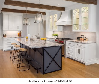 Kitchen in New Luxury Home with Large Island, Hardwood Floors, Range Hood, and Glass Fronted Cabinets, Horizontal Orientation