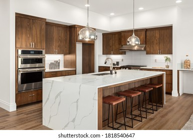 Kitchen in new luxury home with quartz waterfall island, hardwood floors, dark wood cabinets, and stainless steel appliances.