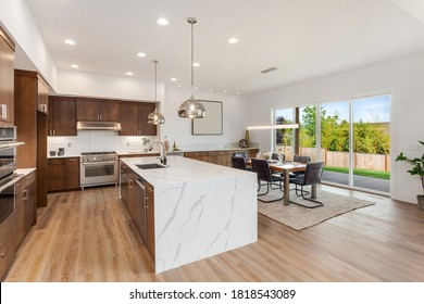 Kitchen in new luxury home with quartz waterfall island, hardwood floors, dark wood cabinets, and stainless steel appliances. Shows view of dining area with large table and place settings.