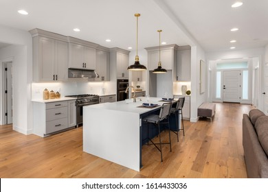 Kitchen in new luxury home with waterfall island, stainless steel appliances, pendant lights, and hardwood floors