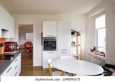 Kitchen with orange tiles and a modern table. Large window with a view. Nobody inside