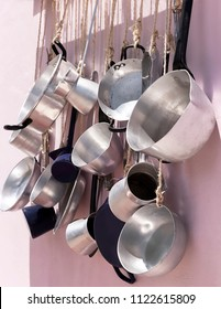 Kitchen pots and pans hanging on a pink wall.  Close-up. Stock Image.