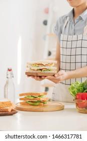 kitchen preparation: Woman making sandwich for breakfast for kids