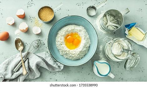 Küche - Teig zubereiten. Schale mit Mehl und Eiern. Grundnahrungsmittel Kochen Zutaten rund (Butter, Milch, Zucker) auf pastellblauem Stein Hintergrund. Von oben (oberste Ansicht, flache Lage) eingefangen.