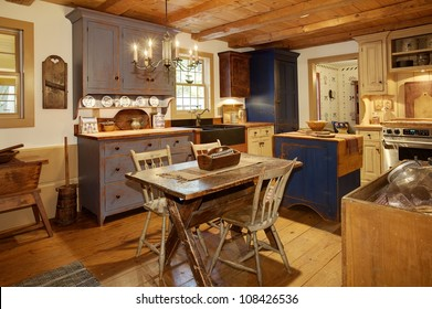 The kitchen in a primitive colonial style reproduction home, built with materials reclaimed from structures built in the late 1700's.  The room contains many antiques from the late 18th century.