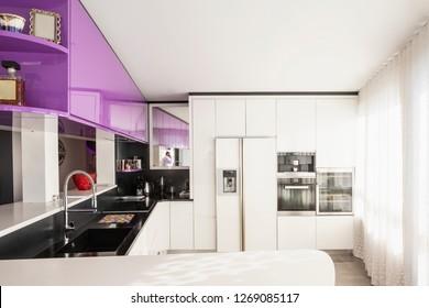 Kitchen with purple and white wardrobe, black counter. Elegant and minimalist. Nobody inside
