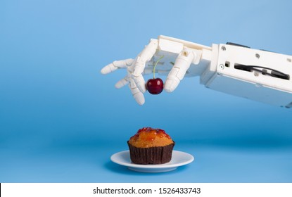 Kitchen robotization. Robot hand putting fresh cherry on top of the cupcake, blue background