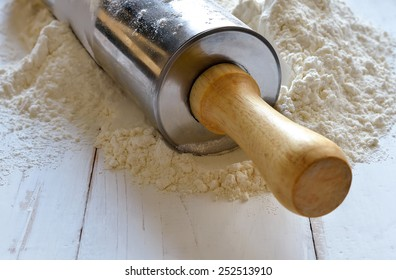 Kitchen rolling pin in a hip of a flour