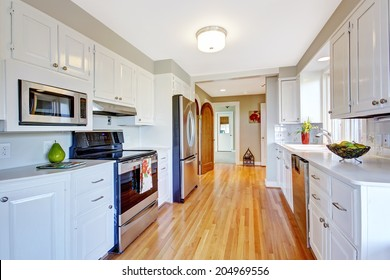 Kitchen room with hardwood floor, white storage combination and steel appliances