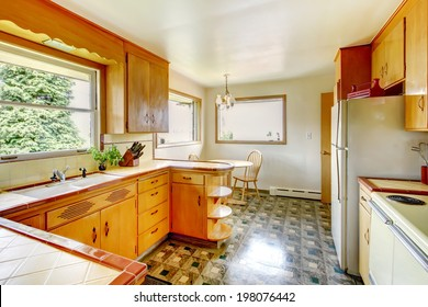 Kitchen room with honey rustic storage cabinets, shiny linoleum floor and small dining area
