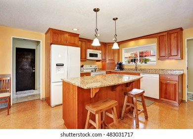 Kitchen room interior with island, wooden cabinets and granite counter top. Northwest, USA