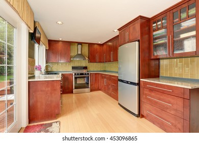 Kitchen room interior with modern brown cabinets and light tones hardwood floor. Also stainless steel appliances and green back splash trim.