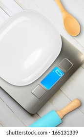 Kitchen scales with digital display on the plank wooden table