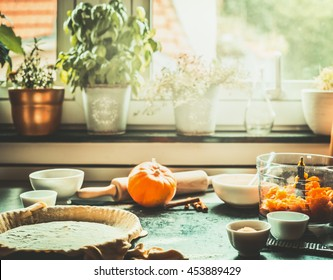 Kitchen scene with preparation of traditional festive pumpkin pie cooking on table at window, retro styled