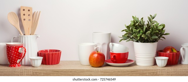 Kitchen shelf with plant, cups, utensils and apples over white wall background