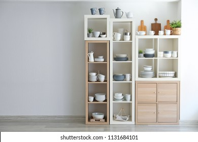 Kitchen shelving with dishes on white wall background