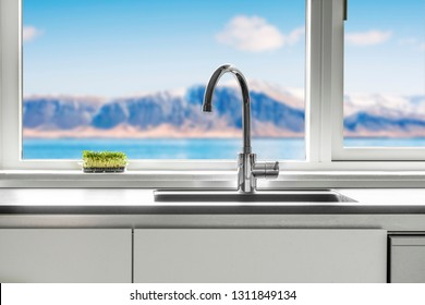 Kitchen sink by a window with a view over the sea and mountains with green cress growing