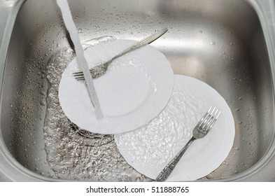 Kitchen sink closeup. In it are white plates, forks and water flows.