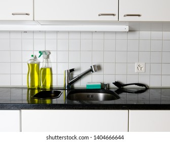 kitchen sink and faucet with a sponge and brush on a black granite table top and yellow kitchen cleaner and dishwashing liquid behind
