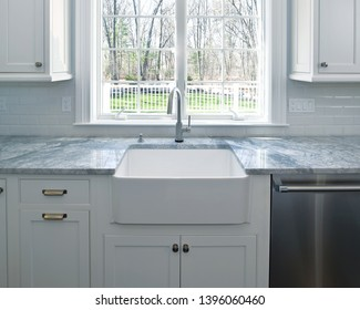 Kitchen sink and marble countertop under sunny window. Home interior, contemporary design.