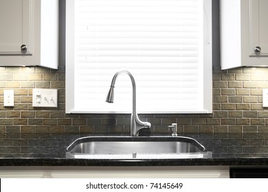 A kitchen sink and window centered in a kitchen