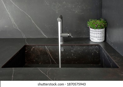 Kitchen sinks made of natural stone. Monolithic design of walls, countertops and sinks made of natural stone. Tap water.