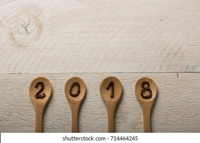kitchen spoon with 2018 subtitle on wooden background