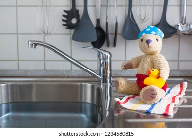 Kitchen stainless steel sink as swimming pool - cute toy teddy bear in swimwear with rubber duck, bathing cap and towel wants to bath (copy space)