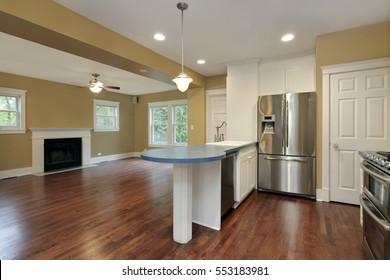 Kitchen in suburban home with view into family room.