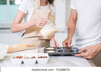 In the kitchen, a sweet couple pouring cake batter, the mixed of flour, milk, and eggs  into the molds for baking cupcakes