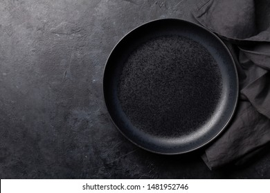 Kitchen table with empty plate and towel. Cooking stone backdrop. Top view with copy space. Flat lay