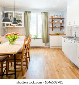 kitchen table in a fancy kitchen with green curtains and wooden floor