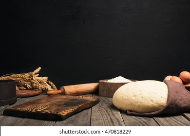 Kitchen table with free place for your product and ingredients for cooking bread or pizza. Yeast dough, flour, eggs, wheat and rolling pin on the wooden table