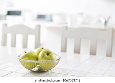 Kitchen table with green apples