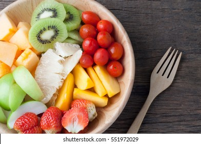 kitchen table with Variety of Fruits on wood plate and fork, group of Fruits salad - healthy eating and dieting food, concept of health care,  Image focus top view.