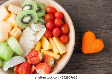 kitchen table with Variety of Fruits on wood plate and heart shape, group of Fruit salad - healthy eating and dieting food, concept of health care, right copy space for text, Image focus top view.