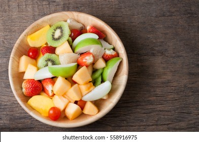 kitchen table with Variety of Fruits on wood plate, group of Fruit salad - healthy eating and dieting food, concept of health care, right copy space for text, Image focus top view.