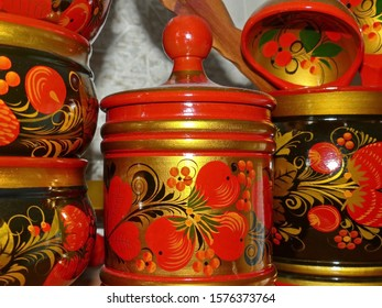 Kitchen tableware and wooden spoons. Closeup. Khokhloma - an ancient Russian folk craft XVII century. Traditional elements Khokhloma - red juicy berries of mountain ash and wild strawberries