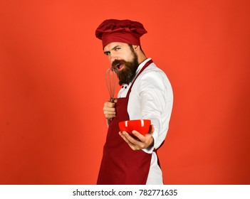 Kitchen tools concept. Chef with red plate and whipping utensil. Cook with seductive face in burgundy hat and apron holds bowl and whisk. Man or hipster with beard holds kitchenware on red background