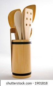 Kitchen tools, including wooden spoons, wire whisk, bamboo tongs, and bamboo stir fry utensils in a bamboo holder, adorned with black cording.