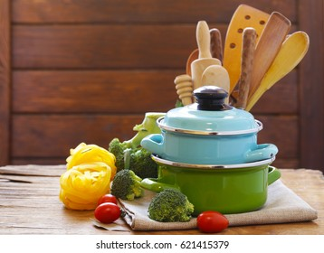 Kitchen tools - pots and cutlery on a wooden table