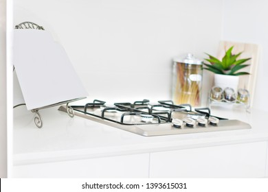 Kitchen tools with white walls and cooker, perfect lightning, evening time at kitchen, gas cooker also some glass bottles on pantry table.