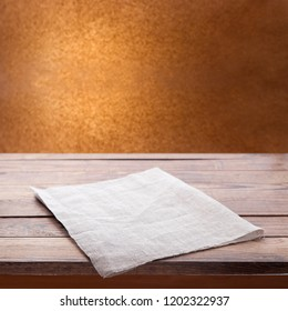 Kitchen towel on empty wooden table on kitchen interior background. Napkin close up top view mock up for design. .