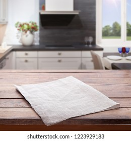 Kitchen towel on empty wooden table on kitchen interior background. Napkin close up top view mock up for design.  Selective focus.