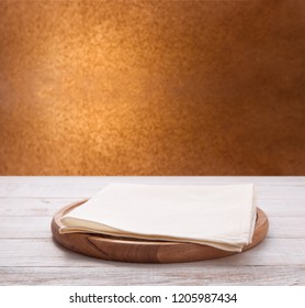 Kitchen towel and pizza board on wooden table. Napkin close up top view mock up for design. Kitchen rustic background.