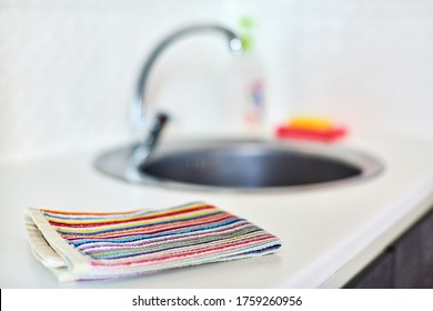 Kitchen towel and sink without dirty dishes background. Dishcloth on kitchen countertop. Cleaning and dish washing concept.