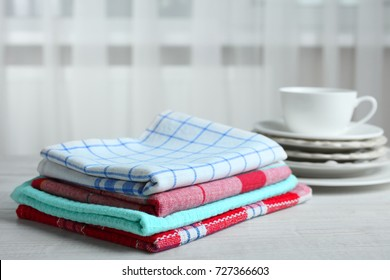 Kitchen towels and dishes on a wooden table in the background of the window.