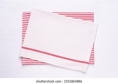 Kitchen towels or napkins on white wooden table top. Mock up for design. Top view