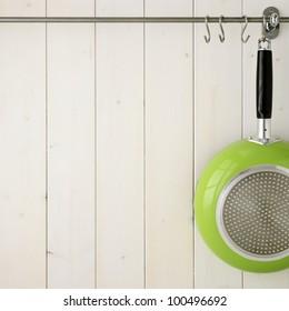 Kitchen utensil on steel rack against white wooden wall