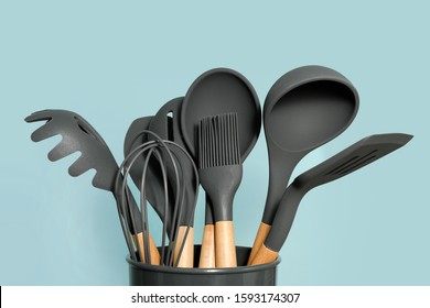 Kitchen utensils background with copyspace, home kitchen decor concept, kitchen tools, rubber accessories in container. Restaurant, cooking, culinary, kitchen theme. Silicone spatulas and brushes